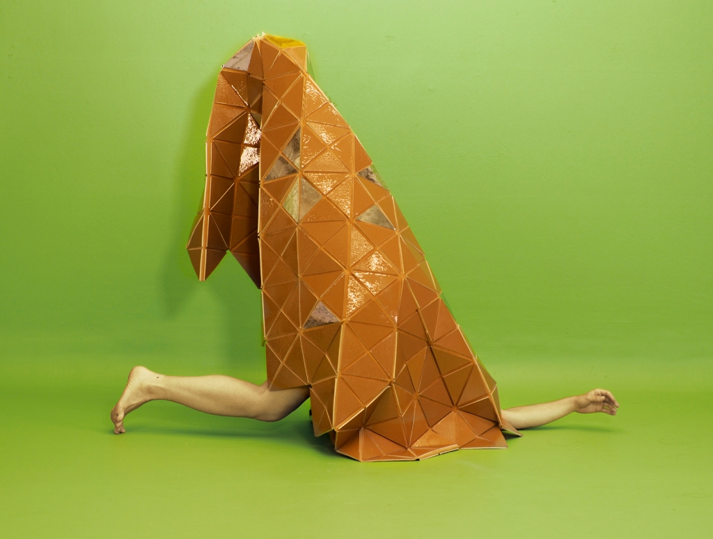 A rust colored solid patchwork quilt-like sculpture with the dancer's lower leg and one forearm protruding, on a green background.