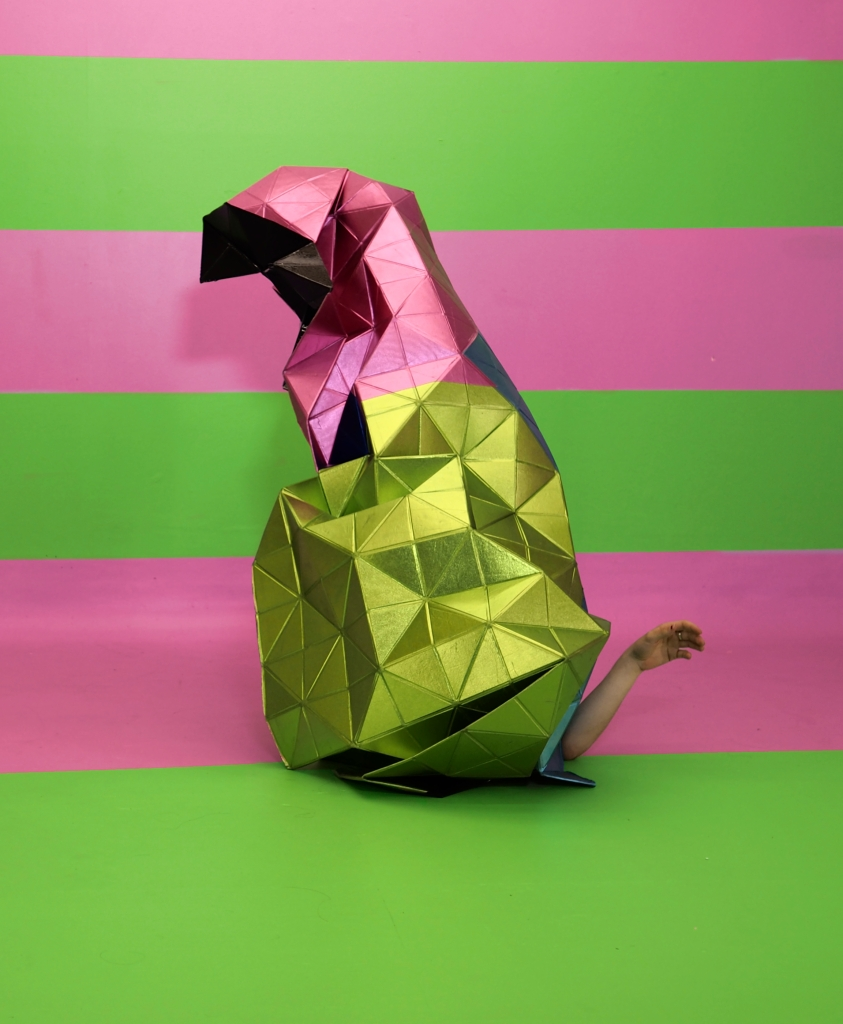 pink and green metallic sculpture folded like a creature with arm at the base like a tail, on pink and green background