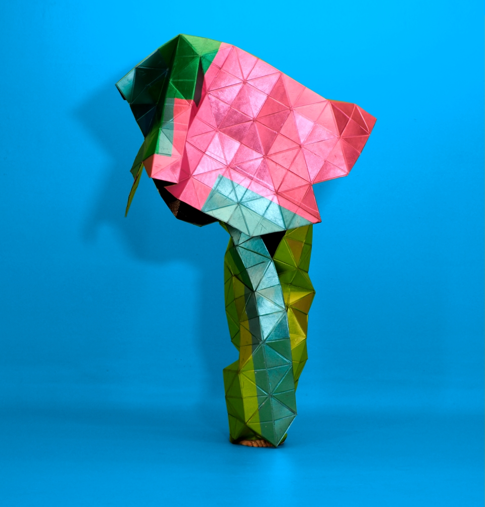 pink and green metallic sculpture on blue background, toes peeking out from the base.