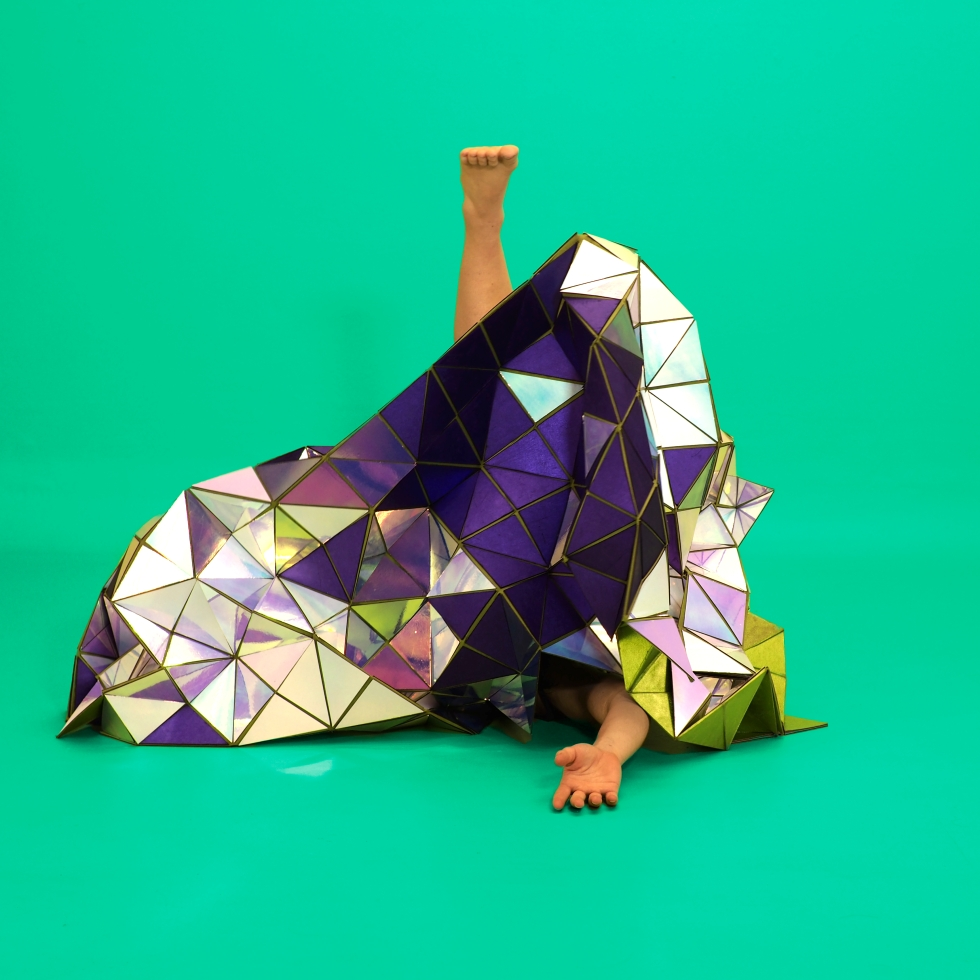 A geodesic tapestry made of mirror triangles and purple fabric, with Lucy Fandel's foot and arm visible.
